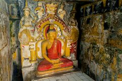 Meditation of Buddha statue with guards in ancient fresco walls of 14th century temple in Sri Lanka Stock Image