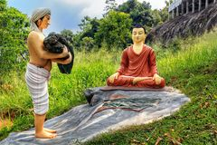 Sculptural composition man brought an offering to Buddha. Kandy, Sri Lanka - January 9, 2018. Sculptural composition man brought an offering to Buddha Royalty Free Stock Image