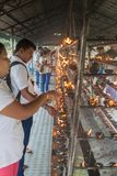 KANDY, SRI LANKA - JULY 19, 2016: White clothed Buddhist devotees light candles at the Temple of Sacred Tooth Relic. During Poya Full Moon holiday royalty free stock photography
