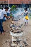 KANDY, SRI LANKA - JULY 19, 2016: White clothed Buddhist devotees light incense sticks at the Temple of Sacred Tooth. Relic during Poya Full Moon holiday royalty free stock image