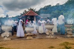 KANDY, SRI LANKA - JULY 19, 2016: White clothed Buddhist devotees light incense sticks at the Temple of Sacred Tooth. Relic during Poya Full Moon holiday stock image