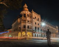 Kandy sri lanka queen`s  hotel at night with traffic light trails and a police man stock photo