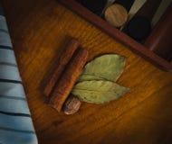 Kaneel, notemuskaat en baaibladeren op een houten lijst stock fotografie