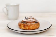 Kaneelbroodje met rozijnen in een ceramische schotel Royalty-vrije Stock Foto's