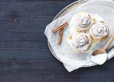 Kaneelbroodjes met roomkaassuikerglazuur en pijpjes kaneel op a Stock Foto