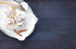 Kaneelbroodjes met roomkaassuikerglazuur en pijpjes kaneel op a Stock Afbeelding