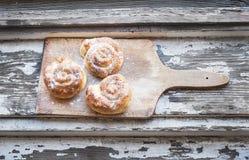 Kaneelbroodjes op een rustieke houten raad Royalty-vrije Stock Afbeelding