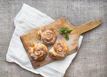 Kaneelbroodjes op een rustieke houten raad over een juteoppervlakte Royalty-vrije Stock Foto