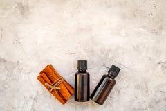 Kaneelolie voor het koken, aromatheraphy, huidzorg Flessen dichtbij pijpjes kaneel op grijze ruimte als achtergrond voor tekst royalty-vrije stock foto