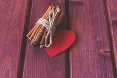 Kaneelvoorraden met hart op houten planken Stock Afbeelding