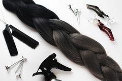 Kanekalon人为Ombre头发黑和灰色在白色背景顶视图接近的clipsa梳子和浪花 免版税库存图片