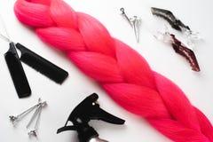 Kanekalon-Haar hochrot oder rosarot auf weißen nahen Clipn der Draufsicht des Hintergrundes ein Kamm und der Spray lizenzfreie stockfotos