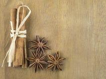 Kanelbrun pinnar som är förbundna med torrt gräs och blommor av anis på trätabellbeiga Arkivfoton