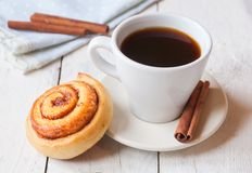 Kanelbrun rulle med kaffe royaltyfria foton
