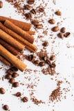 Kanelbruna pinnar, coffebönor och partiklar av choklad Arkivbild