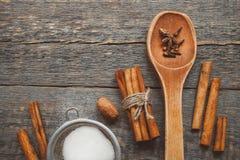 Kanelbruna pinnar, en sikt med en sked av socker och krydda royaltyfri foto
