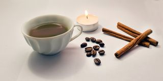 Kanelbruna pinnar, kaffebönor som tänds stearinljus, en kopp kaffe Royaltyfri Bild