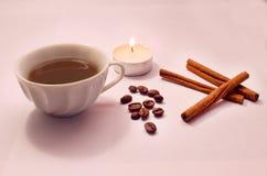 Kanelbruna pinnar, kaffebönor som tänds stearinljus, en kopp kaffe Arkivbilder