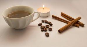 Kanelbruna pinnar, kaffebönor som tänds stearinljus, en kopp kaffe Royaltyfria Foton