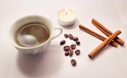 Kanelbruna pinnar, kaffebönor som tänds stearinljus, en kopp kaffe Royaltyfri Foto