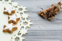 Kanelbruna pinnar med kakor för anisstjärna- och kanelstjärnor på träbakgrund Royaltyfria Foton