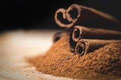 Kanelbruna pinnar med kanelbrunt pulver på trä Royaltyfria Foton
