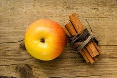 Kanelbruna pinnar och äpple på trätabellingrediensen royaltyfri fotografi