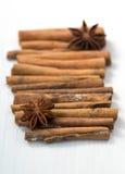 Kanelbruna pinnar och anisstjärnor på vit träbakgrund Royaltyfri Fotografi