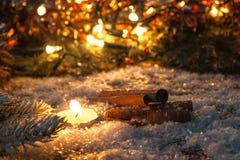 Kanelbruna pinnar och stearinljus i snön på en bakgrund av suddigt ljus Royaltyfri Fotografi