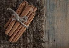 Kanelbruna pinnar samlar ihop bundet med repet på en mörk bakgrund royaltyfri foto