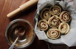 kanelbruna rullar Nytt bakade kanelbruna bullar med kryddor och kakaofyllning på pergamentpapper Top beskådar Söt hemlagad bakels fotografering för bildbyråer