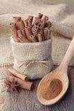 Kanelbrunt pulver och kanelbruna pinnar i säckväv hänger löst Arkivfoto