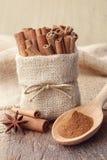 Kanelbrunt pulver och kanelbruna pinnar i säckväv hänger löst Arkivbild