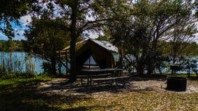 Kanfas en ramtältplats med den Pinic tabellen, brand Pit Lake Side royaltyfria foton