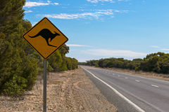 Kangaroo crossing road sign next to the road on Princess Highway. Soft focus of Kangaroo crossing road sign next to the road on Princess Highway at Coorong Stock Images