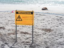 Wildlife warning sign with injured seal on beach stock photos