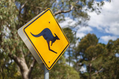 Kangaroo road sign. With Australian bushland in the background. Road signs of koalas, crocs or kangaroos are a popular souvenir for tourists Royalty Free Stock Image