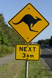 Kangaroo road sign. Next 3 km. Black shilouette of kangaroo on light reflective yellow diamond shaped traffic sign. Background has blue sky footpath with Stock Photo