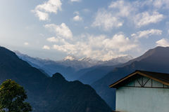Kangchenjunga mountain with clouds above. Among green hills and house that view in the evening in North Sikkim, India Royalty Free Stock Photos
