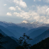 Kangchenjunga mountain with clouds above. Among green hills and trees that view in the evening in North Sikkim, India Stock Photos