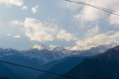 Kangchenjunga mountain with clouds above. Among green hills and trees that view in the evening in North Sikkim, India Royalty Free Stock Image