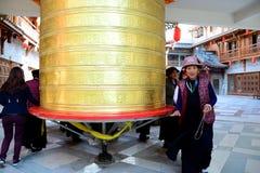 Kangding, China: 1 de octubre de 2013: Torneado de una rueda de rezo de oro Imagen de archivo libre de regalías