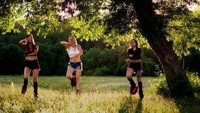 Kangoo del entrenamiento del grupo Tres muchachas en la puesta del sol realizan la consolidación dirigida los ejercicios dinámico almacen de video