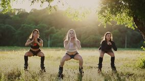 Kangoo del entrenamiento del grupo Tres muchachas en la puesta del sol realizan la consolidación dirigida los ejercicios dinámico almacen de metraje de vídeo