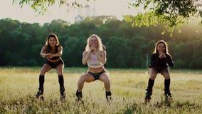 Kangoo di addestramento del gruppo Tre ragazze al tramonto eseguono il dimagramento puntato su edifici occupati dinamici ed il ra video d archivio