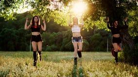 Kangoo di addestramento del gruppo Tre ragazze al tramonto eseguono il rafforzamento del muscolo e di perdita di peso puntato su  video d archivio