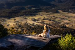 Woman on old timber jetty with Kanimbla valley views in late afternoon sunlight royalty free stock photos