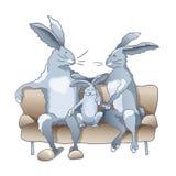 Kaninchenfamilie, die auf dem Sofa sitzt Lizenzfreie Stockbilder
