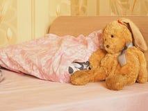 Kaninchenspielzeug auf dem Bett Stockfoto