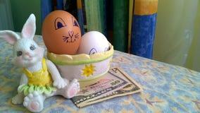 Kaninen leker med easter ägg och pappers- dollar royaltyfria foton